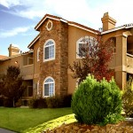 Photo showcasing stucco and stone building exterior with arched windows